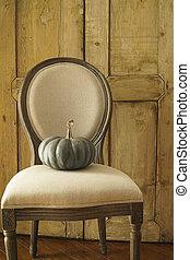 Green pumpkin on chair