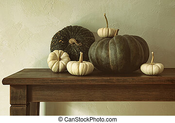 Green pumpkins and small gourds on table