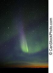 Green-purple streak of aurora over twilight horizon. Many...