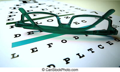 Green reading glasses falling onto eye test in slow motion