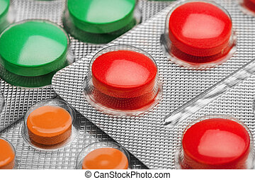 green, red and orange medical pills in plastic packaging ...