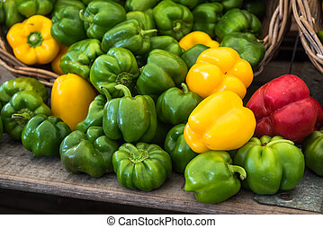 Green, red and yellow bell peppers at the market