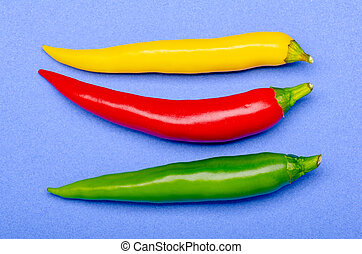 green red yellow chili on blue background