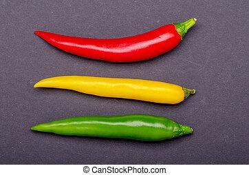 green red yellow chili on dark background
