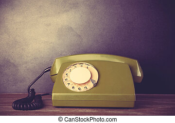 Green retro telephone on a table.