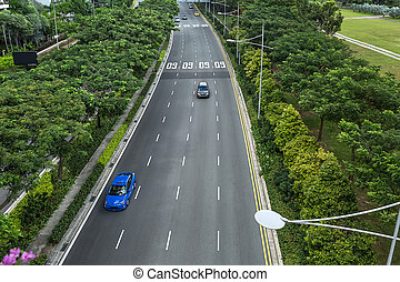 Roadway with four lanes and cars on them in Singapore. On the sides there are street lamps and a lot of green trees. It is an exterior view from the Marina Bay Hotel Sands. Horizontal.
