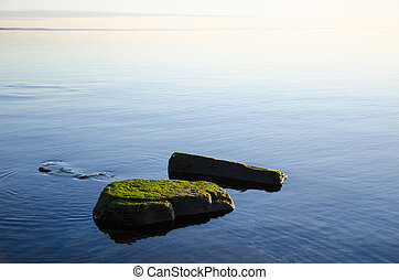 Green rocks in smooth water