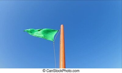 green safe flag waving on a flagpole against a blue clear...
