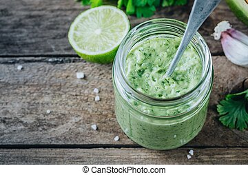 green salad dressing with avocado, lime and cilantro in a glass jar