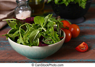 Green salad mix in bowl on wooden table