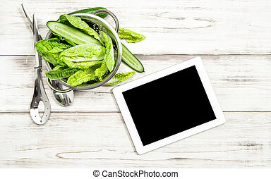 Green salad vegetables with tablet pc on kitchen table