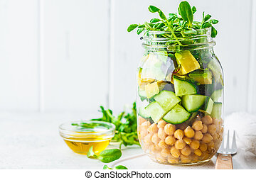 Green salad with chickpeas in a jar, white background, copy space.