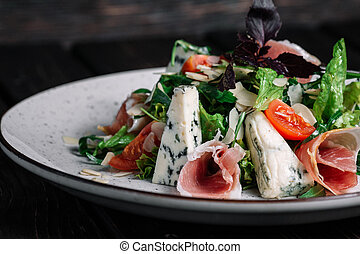 Green salad with prosciutto and blue cheese on dark wooden background