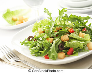 green salad with restaurant setting - delicious green salad...