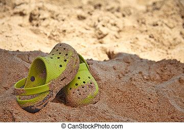 Green sandals on a beach