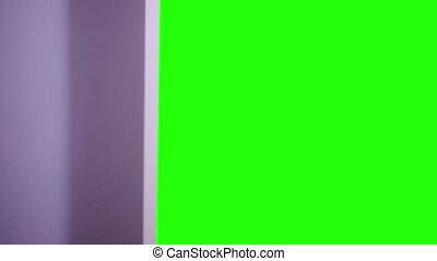 Green screen behind the closet door that is opened by one...