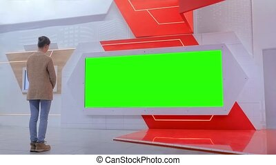 Green screen concept - woman looking at blank large interactive wall display