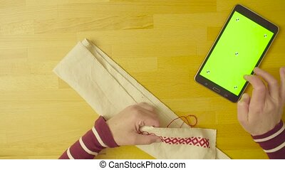 Green screen. Female hands embroidering a pattern - Top...