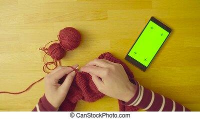 Green screen. Female hands knitting wool - Top view. A...
