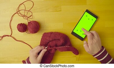 Green screen. Female hands knitting wool - Top view. A...