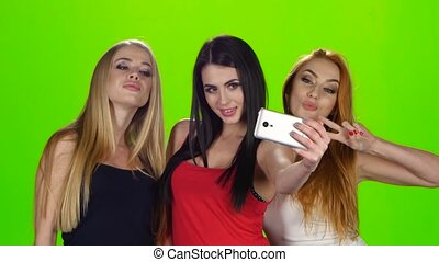 Green screen. Girls pose for the camera of the smartphone