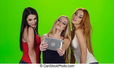 Green screen. Girls pose for the camera of the tablet