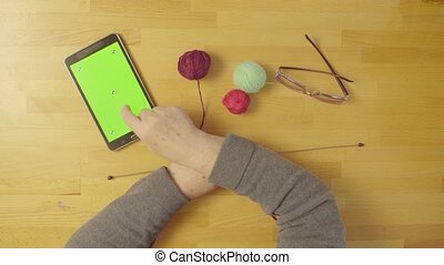 Green screen. Hands of old woman knitting wool - Top view....