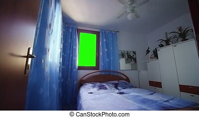 In the room with a double bed, one of the windows is replaced with green to make use of the chroma key, replacing the one you see outside