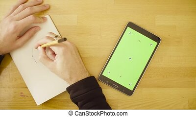 Green screen. Male hands scrolling a tablet - Top view....