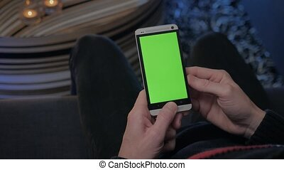GREEN SCREEN man holding his smartphone