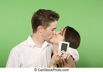 couple kissing holding digital camera over green screen