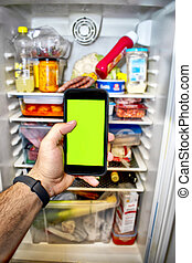 Phone with green screen with the bottom of a refrigerator.