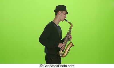 Green screen. Saxophonist playing on the gold musical instrument