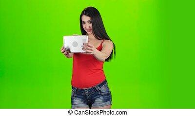 Green screen. Selfie photo brunette using front camera of tablet