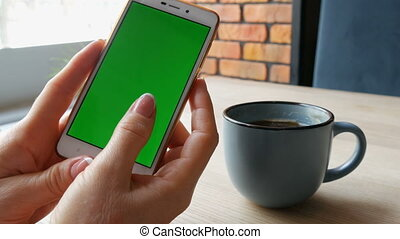 Green screen smartphone. Chroma Key on a white smartphone, female hands hold mobile phone in a cafe next to a cup of coffee