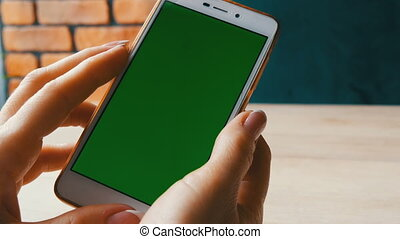 Green screen smartphone. Chroma Key on a white smartphone, female hands hold mobile phone in a cafe