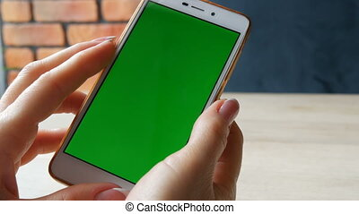 Green screen smartphone. Chroma Key on a white smartphone, female hands hold mobile phone in cafe