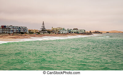 Green sea, waves, coastline with houses in background, Swakopmund German colonial town, Namibia