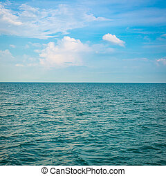 Green sea with waves and clear blue sky