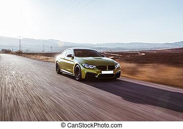 Green sedan car driving on the highway