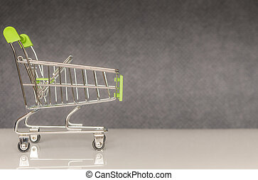 Green shopping cart on a gray blurred background.