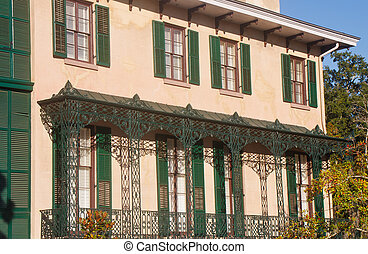 Green Shutters on Old Brown Stucco Building