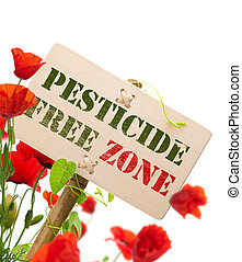 pesticide free zone message on a wooden panel, green plant and poppies - image is isolated on a white background