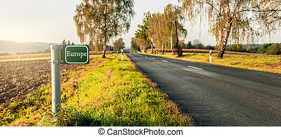 green signboard at the roadside in an autumn landscape.