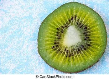 Green slice of kiwi fruit on light blue background