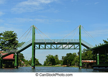 Green sling iron bridge over canal and blue sky