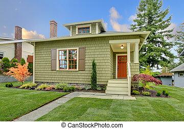 Green cute small craftsman house with orange door