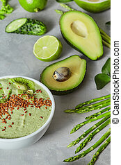 Green smoothie bowl on a light grey slate concrete background.