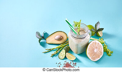 Green smoothie from organic vegetables , fruits, slices of lemon, lime, flax seeds in a glass bowl on blue paper background.