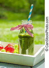 Green smoothie in a bottle with ribbon